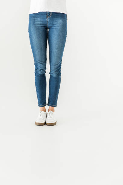 woman in denim pants and shoes standing isolated on white - jeans stock photos and pictures