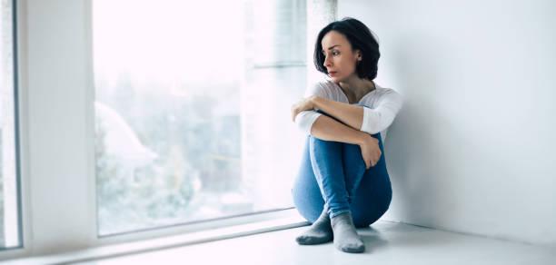 donna in depressione sta guardando attraverso la finestra - assuefazione foto e immagini stock