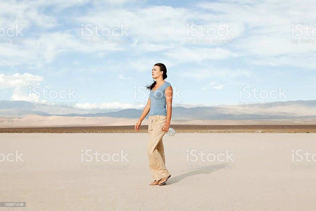Woman in desert landscape with bottle stock photo