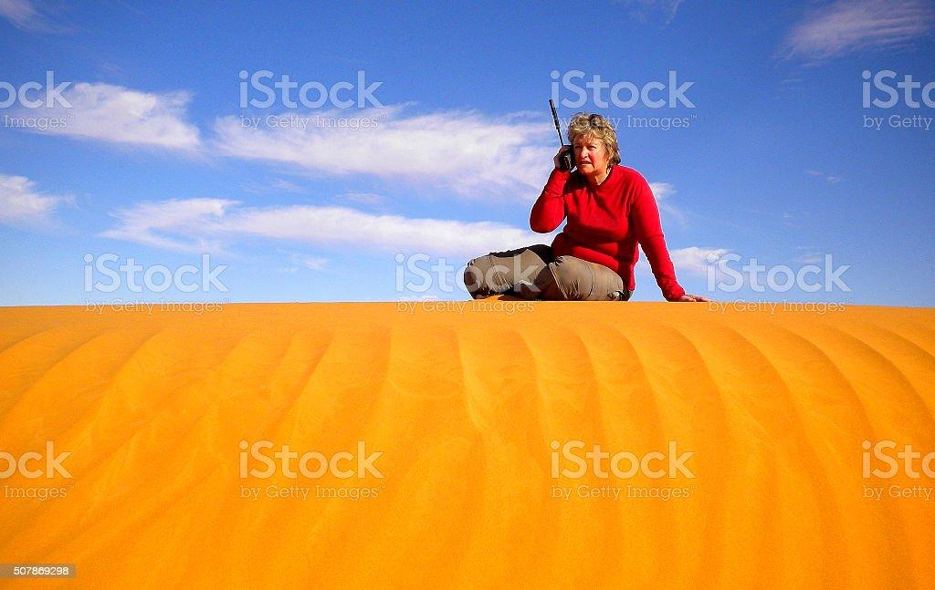 Woman in Desert on Sat Phone stock photo
