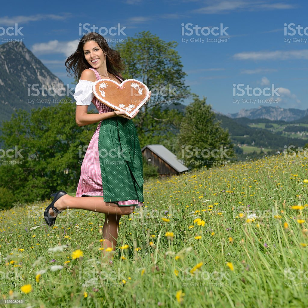 Woman in Dirndl Fashion holding a Lebkuchen Gingerbread Heart (XXXL) royalty-free stock photo