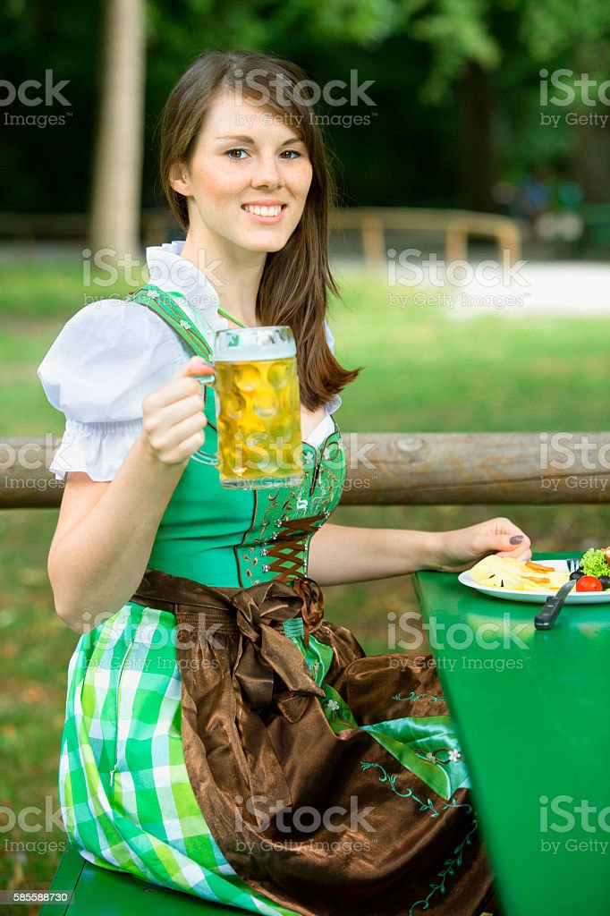 woman in dirndl sitting in beergarden with beer and food – Foto