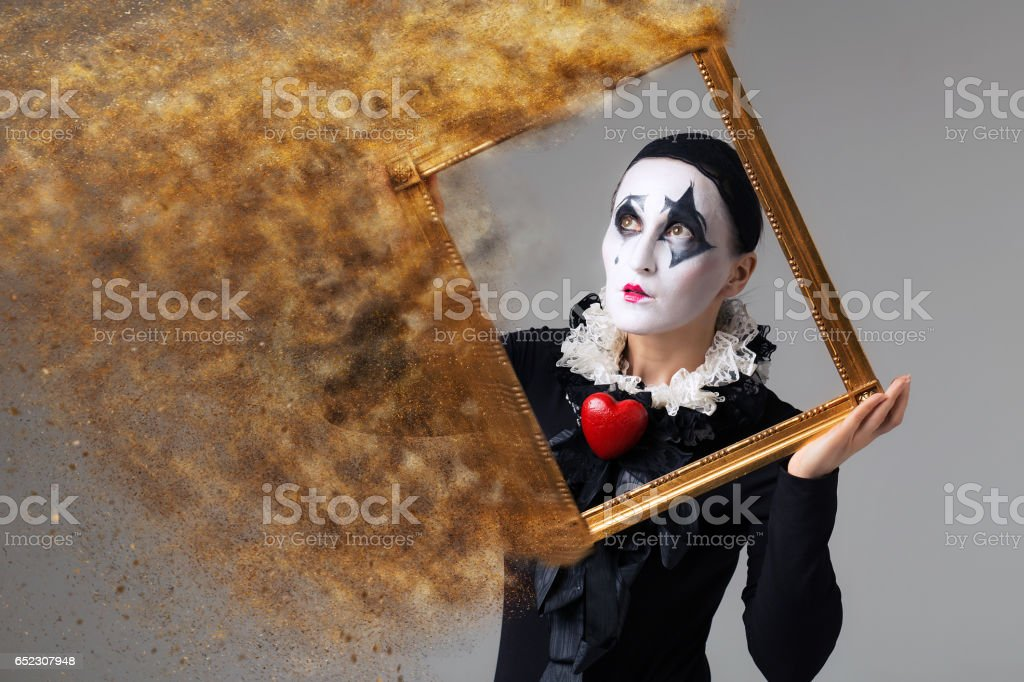 Woman in disguise harlequin in the picture frame. Photo manipulation stock photo
