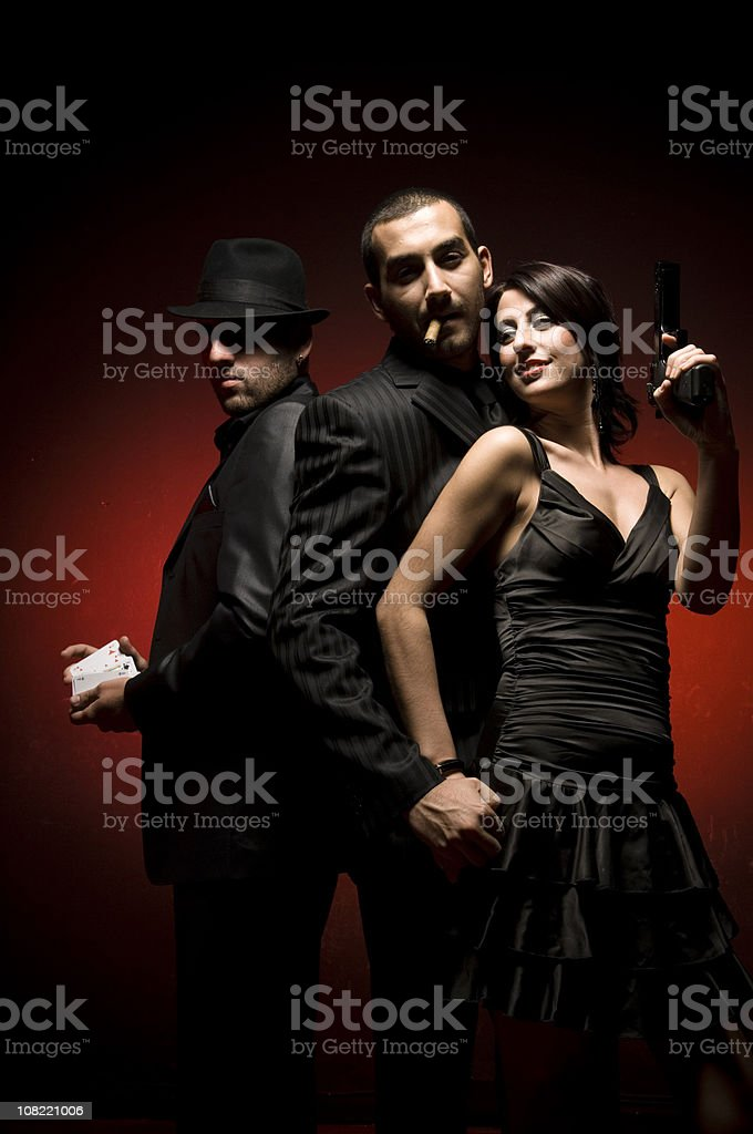 Woman in Dress Posing with Two Men Wearing Black Suits stock photo