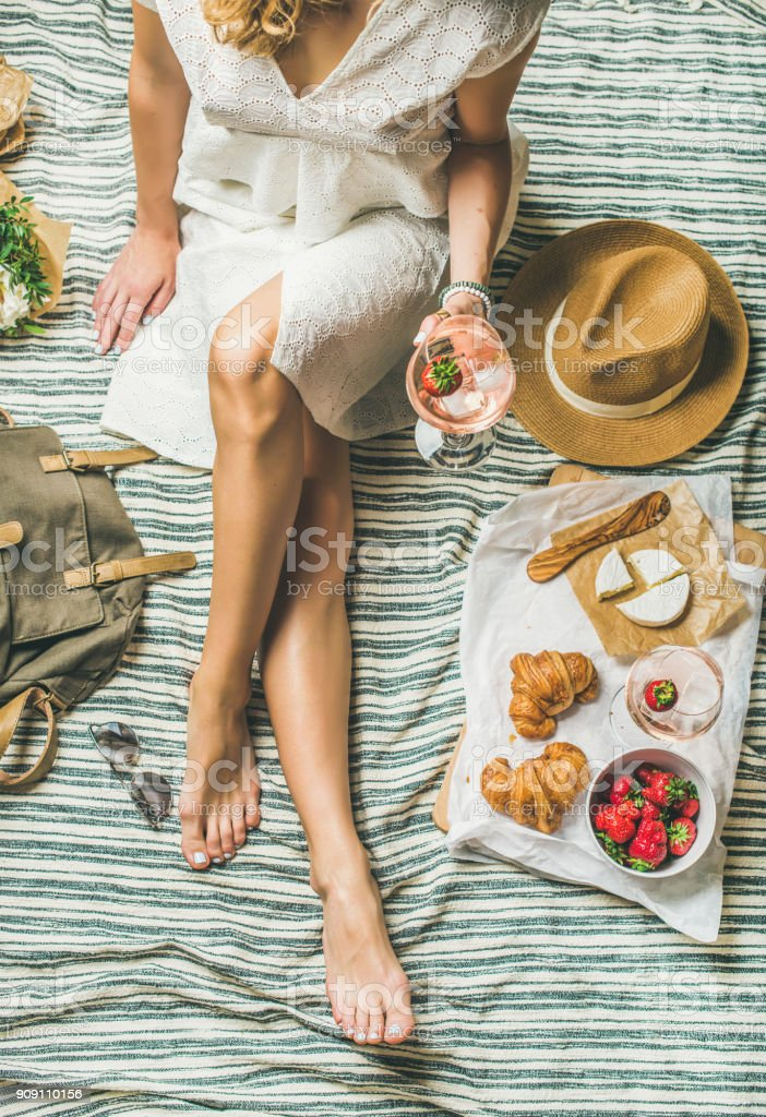 Woman in dress sitting on blanket with wine and snacks stock photo