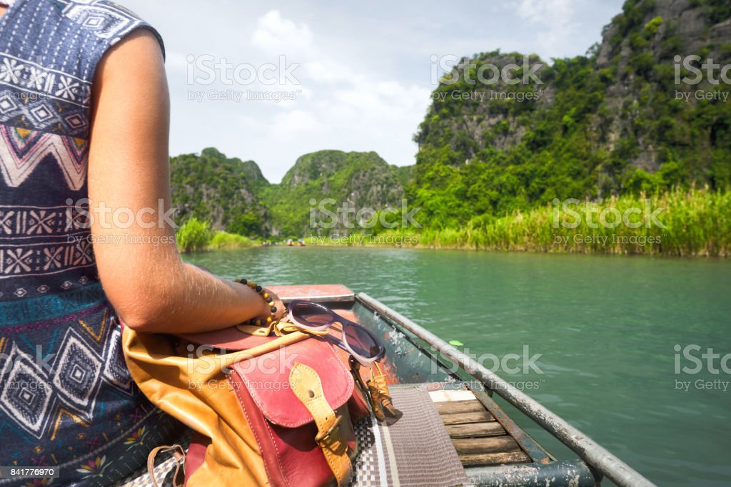 Woman in dress travels on river a background of rocky mountains stock photo