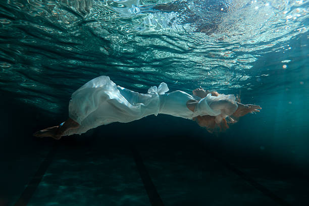 Woman in dress under water. stock photo