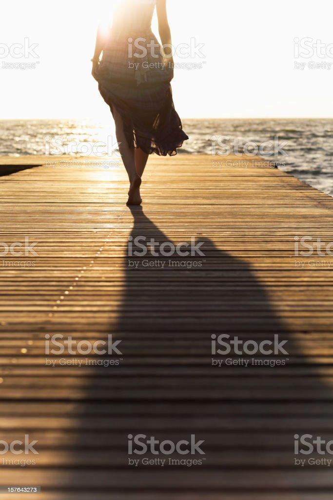 Woman in dress walking barefoot down wooden pier stock photo