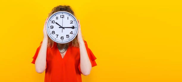 Woman in dress with clocks Portrait of curly-haired woman in red dress and eyeglasses isolated on orange background hiding her face behing big clocks time limit punctuality concept. information sign stock pictures, royalty-free photos & images
