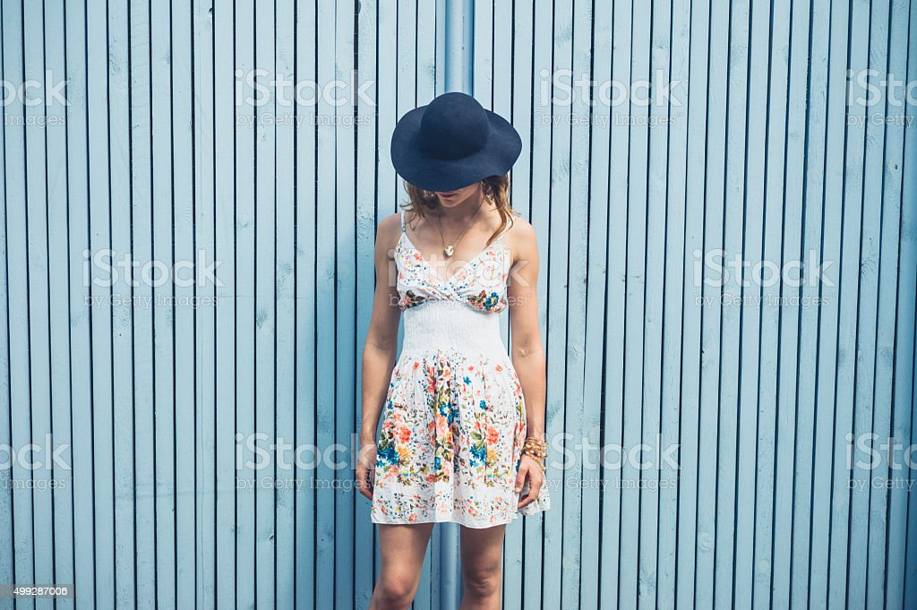 Woman in dress with hat outside by blue fence stock photo