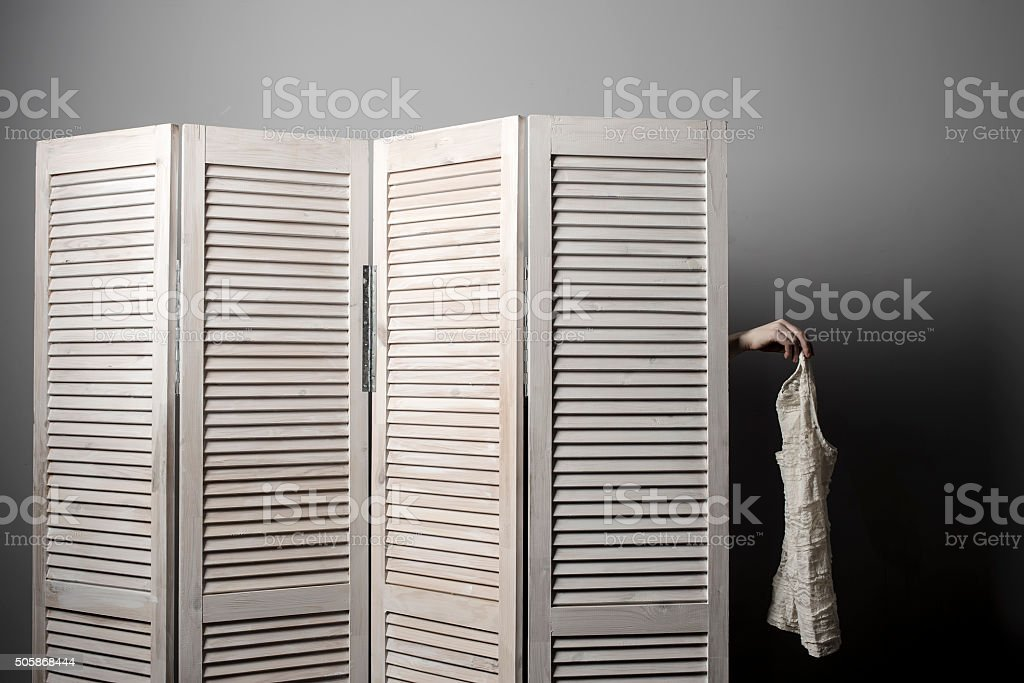 woman in dressing room put arm holds out dress stock photo