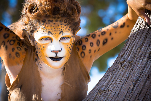 Woman in elaborate jungle cat stage makeup and costume