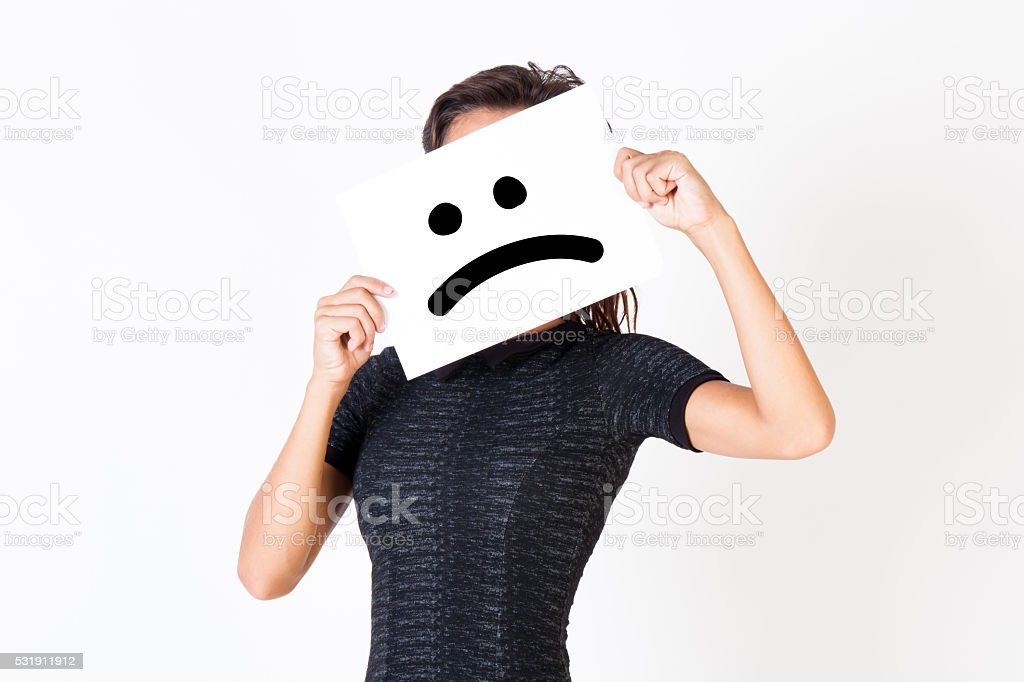 Woman in elegant dress holding dissatisfied face paper stock photo