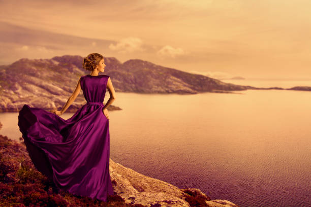 Woman in Elegant Dress on Mountain Coast, Fashion Model in Flowing Gown, Looking Away Woman in Elegant Dress on Mountain Coast, Fashion Model in Flowing Gown Cloth, Looking away to Landscape View, Outdoor evening wear stock pictures, royalty-free photos & images