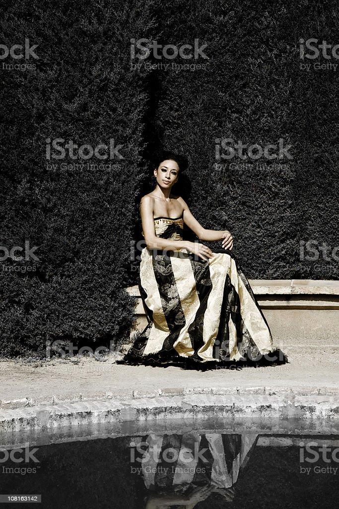 Woman in Elegant Dress Sitting Near Park Fountain royalty-free stock photo