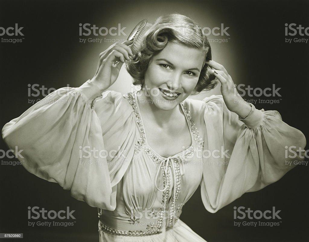 Woman in evening dress brushing hair, (B&W), portrait stock photo