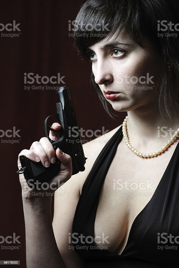 Woman in evening dress holds gun royalty-free stock photo