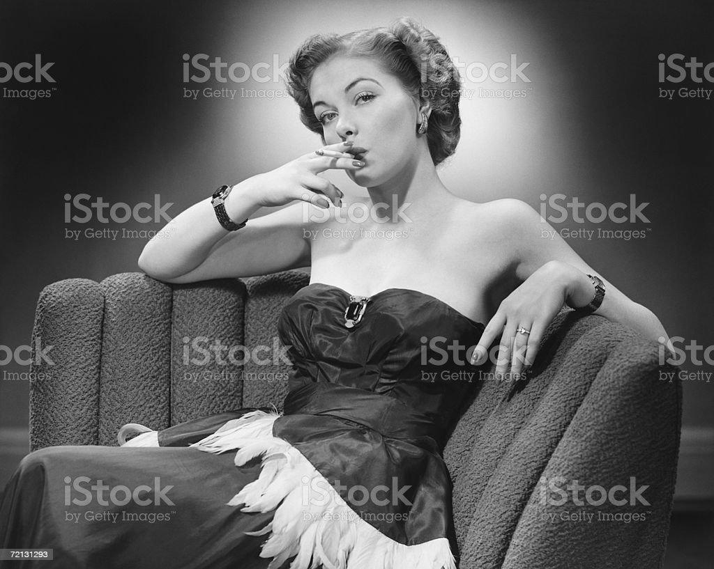Woman in evening dress smoking cigarette (B&W), portrait stock photo