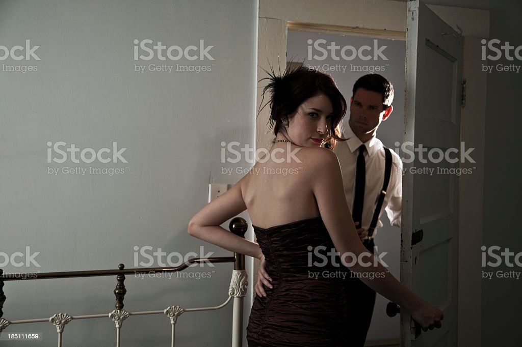 Woman in evening gown, man at door stock photo