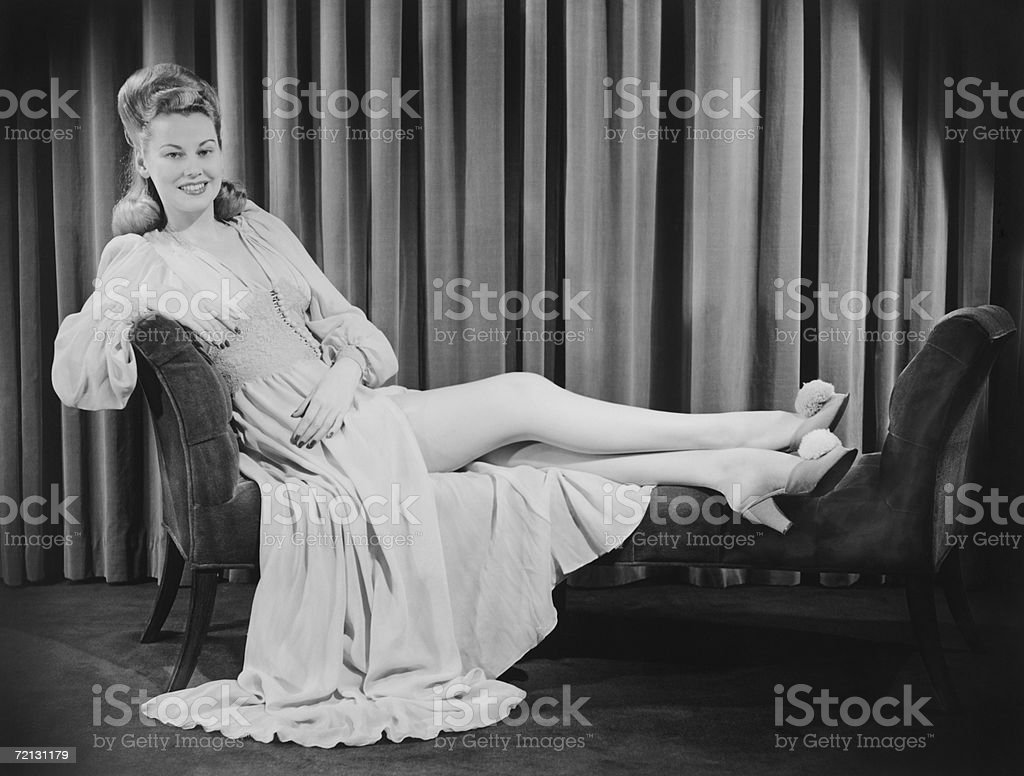 Woman in evening gown reclining on chaise longue (B&W), portrait stock photo