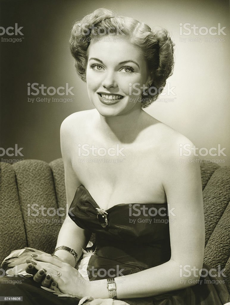 Woman in evening gown sitting on sofa, (B&W), (Portrait) stock photo