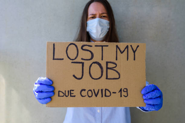 Woman in face mask and gloves with cardboard sign LOST JOB