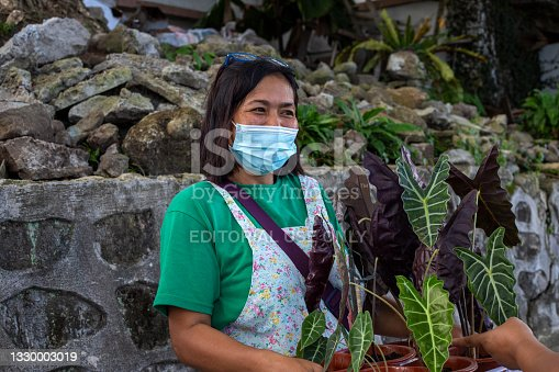 istock Woman in face mask selling flowers . Friendly Filippina in protective mask on market. 1330003019