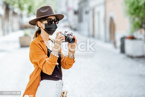 Young female tourist in facial protective mask walking with photo camera on the old city street. Concept of tourism and new social rules and restrictions after coronavirus pandemic