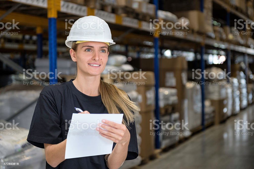 Woman in factory writes and smiles stock photo