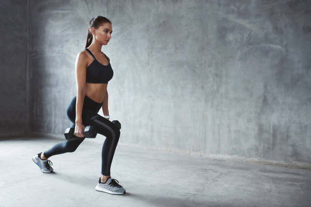 woman in fashion sports clothes training, doing lunges exercise - lunge stock photos and pictures