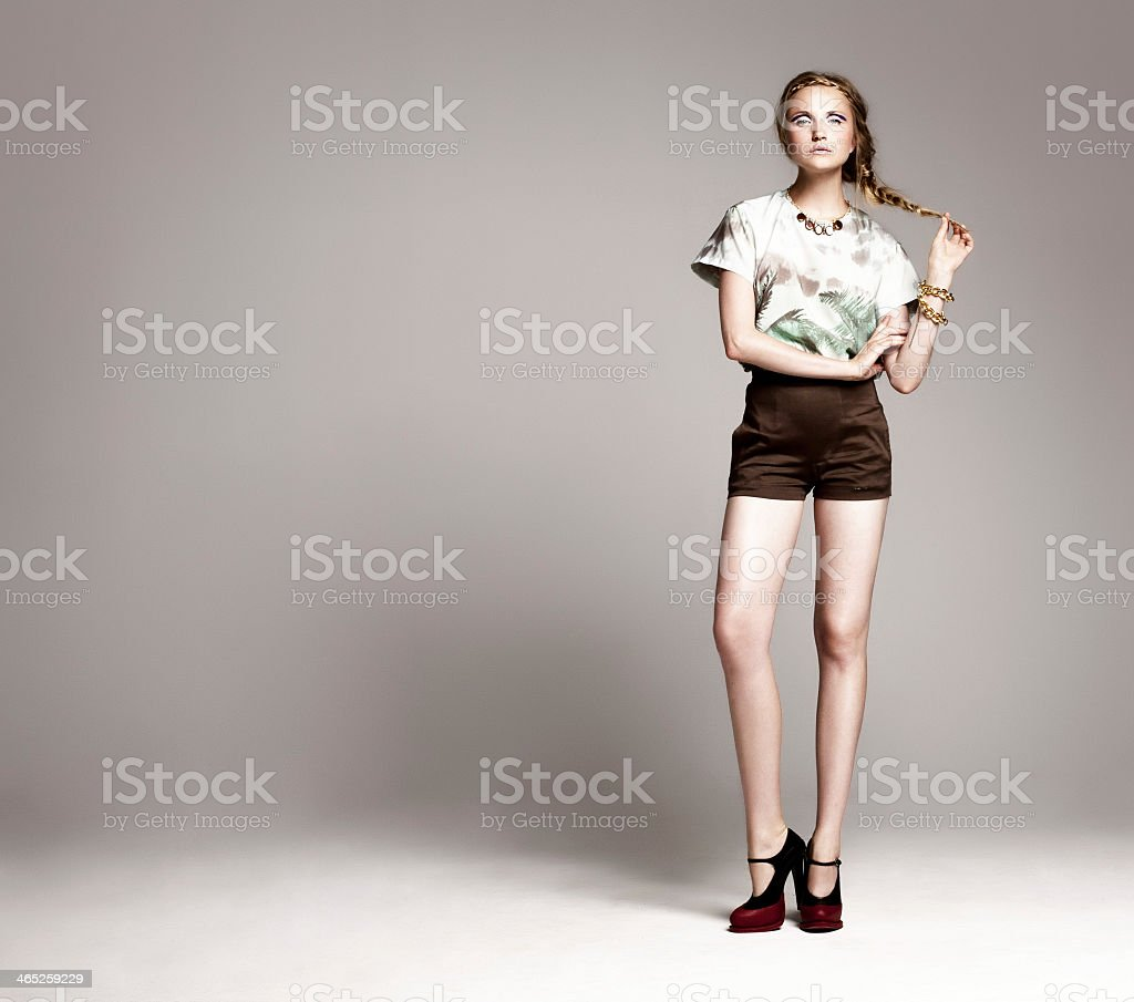 Woman in fashionable clothing standing against gray backdrop stock photo