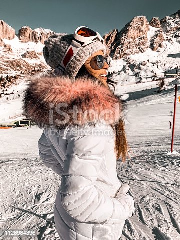 Snowy white winter day in high mountains. Woman in fashionable jacket with fur, ski goggles and sunglasses.