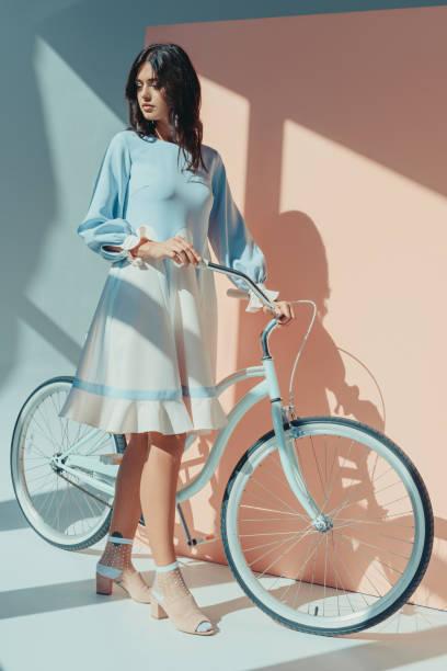 Femme à la robe turquoise avec vélo - Photo