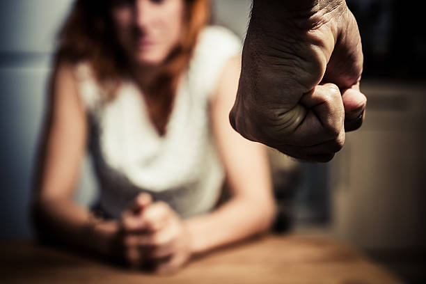 Woman in fear of domestic abuse Young woman is sitting hunched at a table at home, the focus is on a man's fist in the foregound of the image husband stock pictures, royalty-free photos & images