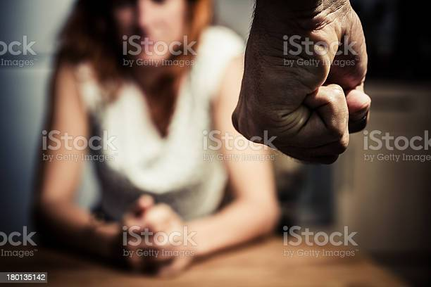 Young woman is sitting hunched at a table at home, the focus is on a man's fist in the foregound of the image