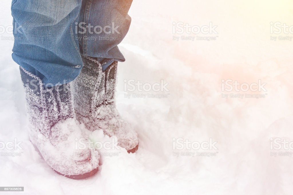 Woman in felt boots standing in the snow stock photo