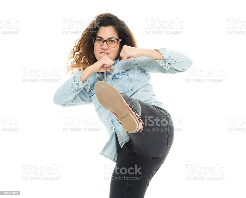 Woman in fighting stance and kicking stock photo