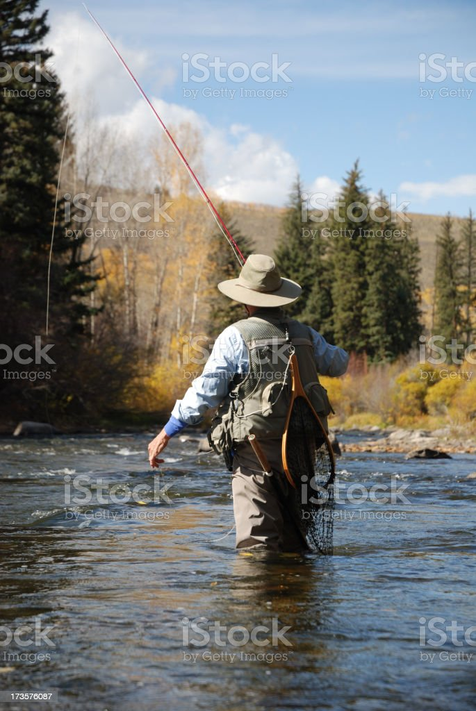 Woman in fishing gear walking in the stream royalty-free stock photo