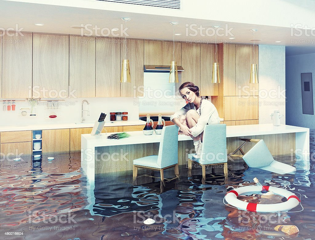 woman in flooded kitchen interior stock photo