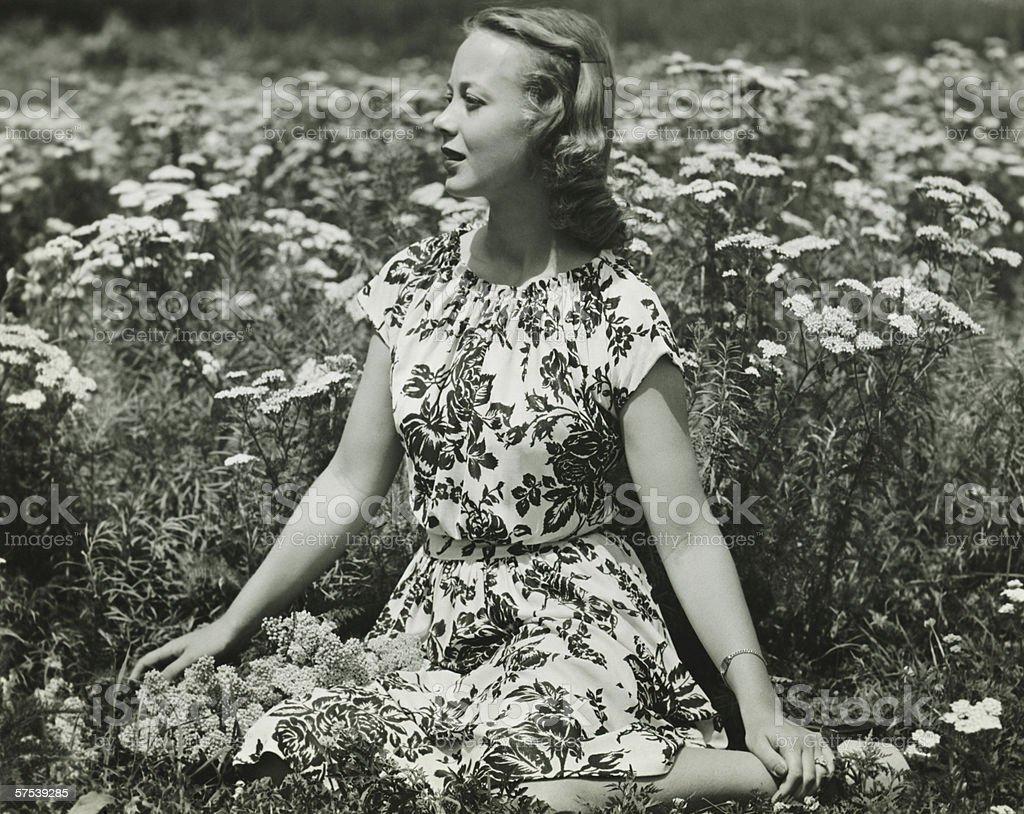 Woman in flowery dress sitting in meadow among flowers, (B&W), portrait stock photo
