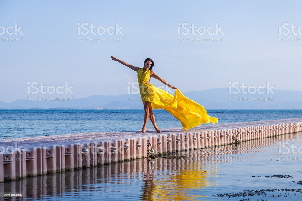 Woman in flying yellow dress on pontoon bridge stock photo