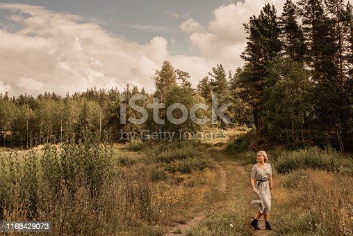 woman in forest woods contemporary modern woman wearing dress and boots in late summer autumn in the nature.