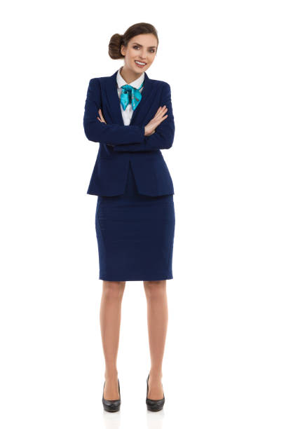 Woman In Formal Business Suit Full Length Young woman in blue formalwear and high heels, standing with arms crossed and looking at camera. Front view. Full length studio shot isolated on white. air stewardess stock pictures, royalty-free photos & images