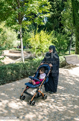 Granada, Spain-July 2017. Arab woman carrying a cart with a baby in the gardens of the Alhambra. The Alhambra is an Andalusian palatine city located in Granada, autonomous community of Andalusia, Spain.  You can see the life of arab tourist with children.