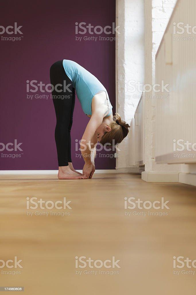 Woman in forward bending Yoga pose royalty-free stock photo