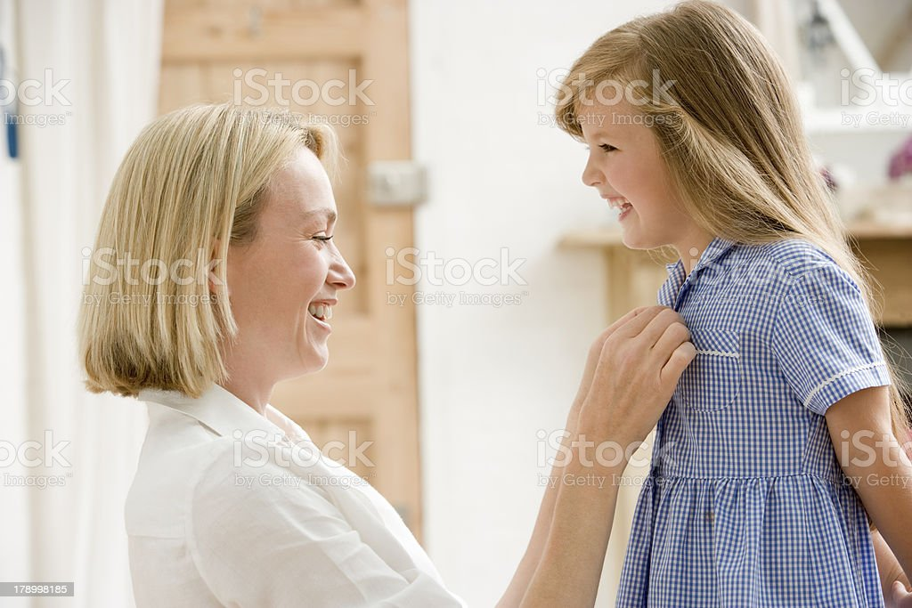 Woman in front hallway fixing young girl's dress stock photo
