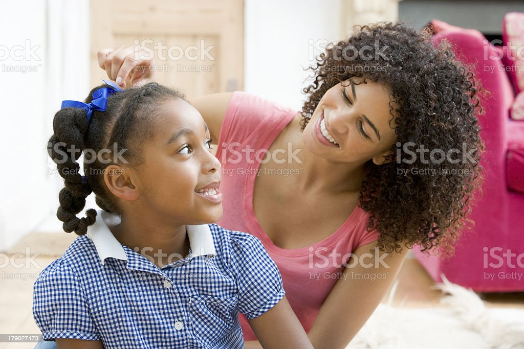 Woman in front hallway fixing young girl's hair stock photo
