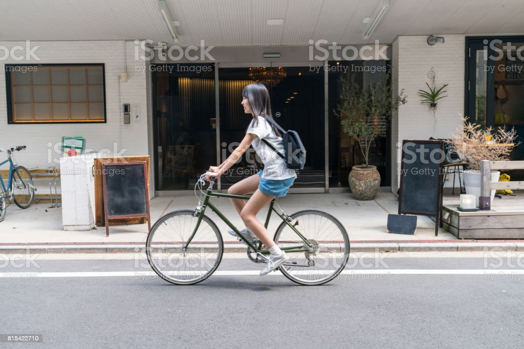 Woman in front of a hotel with a rental bicycle stock photo