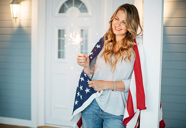 Woman in front of a house. Woman standing on a porch of her house, American flag is on her shoulders. Holding sparkler. one mid adult woman only stock pictures, royalty-free photos & images