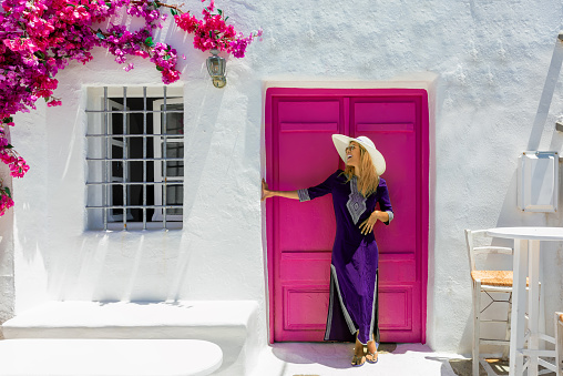 Woman in front of a traditional cylcadic house in Paros, Greece